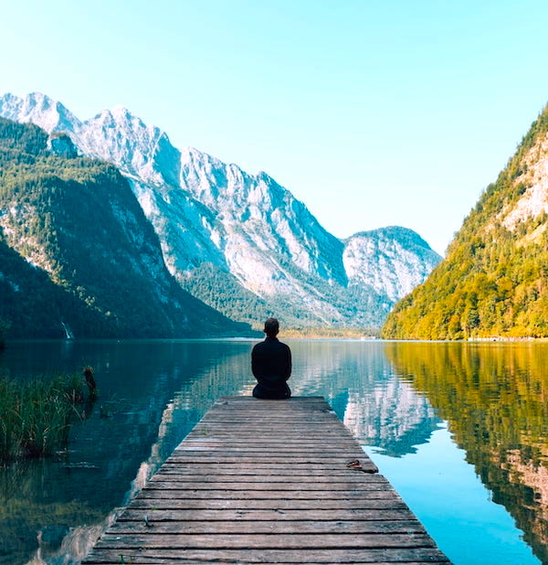 Man sitting on dock looking at mountains